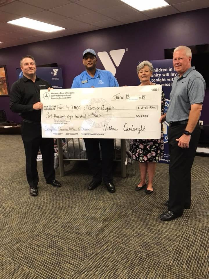 The general manager and event coordinator for Mercedes-Benz Augusta giving their donation to the YMCA (Source: YMCA)