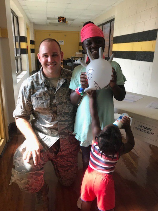 A service member poses with patients at Thomsons Innovative Readiness Training event (Source: Master Sgt. Theanne Hermann