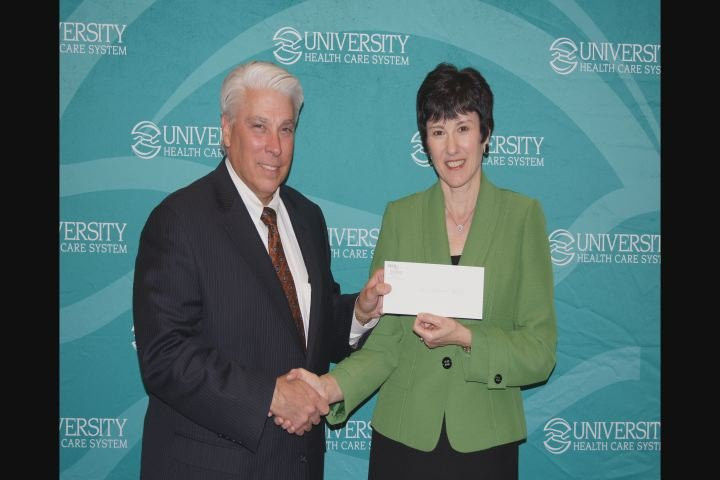 University Health Care System President/CEO James R. Davis presents a check for $50,000 to ATC President Dr. Susan Winsor .