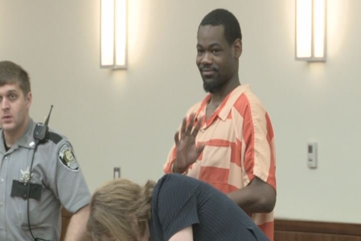 Kevin Richardson smiles and waves to family members in the courtroom.