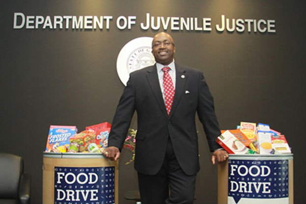 DJJ Commissioner Avery D. Niles stands with food collected during the agency's first statewide food drive. (Source: Georgia DJJ)